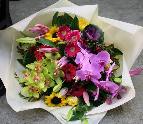 An Assorted bouquet of Brightly mixed coloured Flowers.  Including sunflowers, gerberas, lilies, and freesias