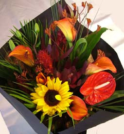 Tropical bouquet of Antheriums, sunflowers, Calla lilies and assorted foliage