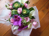 Seasonal pinks, greens and whites and folded Flax in a water box.