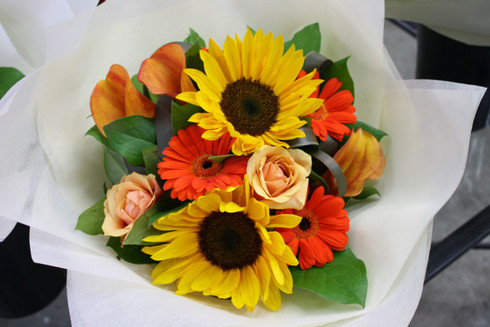 Bright mixed assorted bouquet including roses, sunflowers and other seasonal blooms.