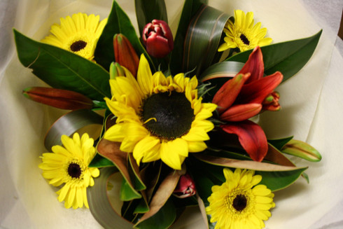 Reds and yellows to include sunflowers, gerberas and lilies with seasonal greens.