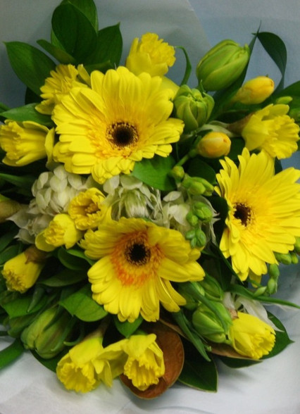 Yellow seasonal blooms and greenery. We a spring flower base in Winter/spring and then callas and sunflowers in summer