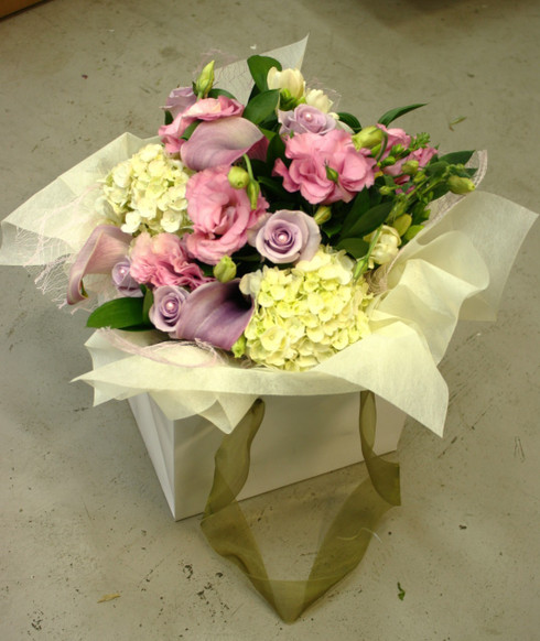 Vintage styled posy in a carry bag, colour tones of pale pinks, purples and whites.