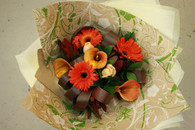 Burnt Oranges and Red including gerberas, roses, calla lilies and flax's create a Autumn toned bouquet
