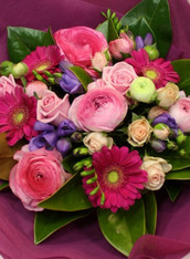 Hand tied bouquet of bright and pale pink flowers with a splash of lavender, includes freesias, roses, gerberas and the best of the best of the seasonal blooms.