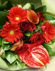 Romantic bouquet in seasonal red blooms, includes red roses and gerberas.