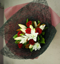 Handtied bouquet of 6 white lilies and 6 red roses.