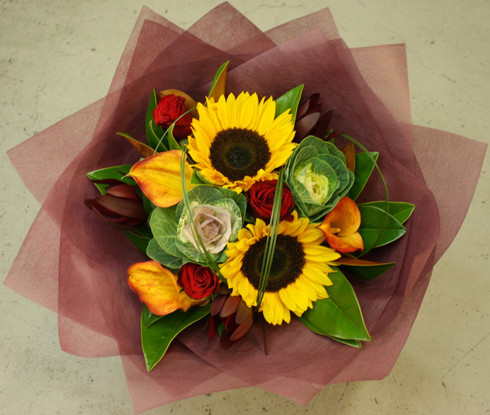 Red roses, sunflowers and calla lilies with seasonal fillers and magnolia foliage.   When sunflowers are not available gerberas will be used.