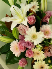 Bouquet of pale pinks and whites incs oriental lilies with roses and geberas seasonal fillers and magnolia foliage.