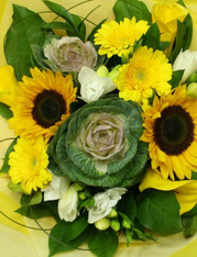 Bouquet of Sunflowers, freesias, callas and kale in bright yellows and whites.