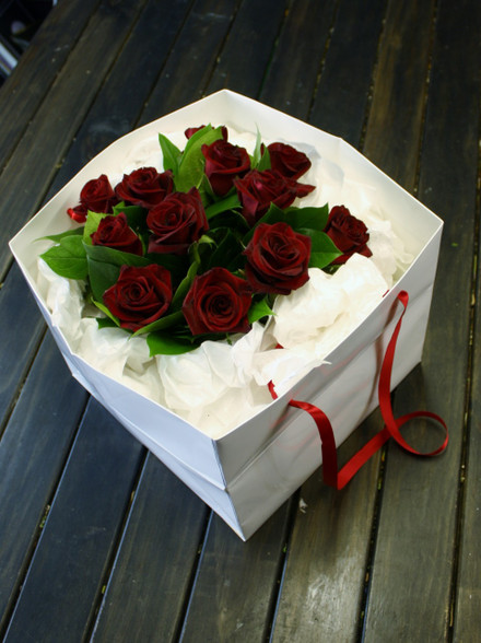 Dozen short stem red roses with foliage in a carry bag surrounded in tissue paper.