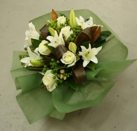 Oriental Lillies and roses with mixed seasonal foliages, if we have freesias in stock we'll include them as well! creating a lovely scented bouquet.