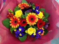 Bright seasonal bouquet in Reds,Oranges and blues  Includes gerberas, Iris and roses