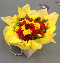 Seasonal bouquet in a bag.  Includes Roses and Gerberas and other seasonal blooms   Based round our popular best seller 'Courtenay' but in yellows and reds.