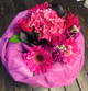 A Seasonal bouquet Wrapped in Pink with Seasonal flowers in pinks.