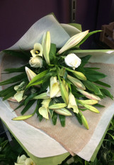 Christmas lilies, Callas and white roses backed with fresh green foliage's. Wrapped naturally in neutral colours.