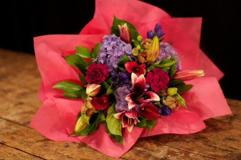 Bouquet of lovely deep pinks, purples with lush greenery  Delivered with a wet wrap on the stems to keep the flowers fresh.