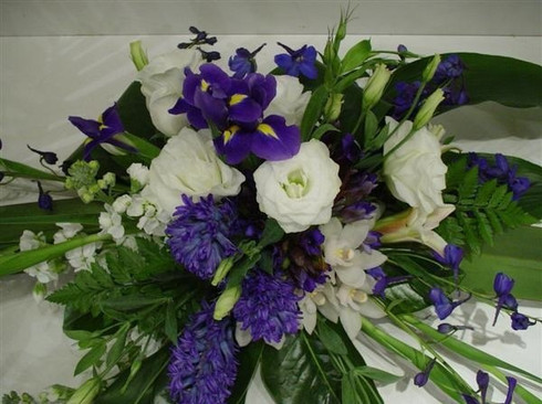 Blues and whites with fresh foliage. This arrangement is in Oasis a floral foam which holds water.