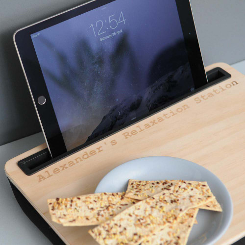 In bed, on the train, the garden shed... they take their iPad everywhere, don't they? Our Engraved Wooden iBed Lap Desk will allow them to surf the net in comfort.  Engraved with a personal Message, this cool tablet lap desk will make a unique and handy gift for iPad users who are always on the go. Ideal for using around the home or out and about, the handy lap desk is complete with a cushioned backing for comfort and to prevent movement together with a wide lip at the back to secure the tablet. The desk itself is perfect for perching a cuppa, sandwich or paperwork on! The ultimate pressie for students, travellers and other iPad users. Your Gift Personalised  You can personalise your lap desk with Any Message up to 30 characters long. General Information      Tablet lap desk with wooden top and a cushioned backing made from spandex and microbeads     Measures 34 x 24 x 5cm     Please note accents and symbols cannot be engraved