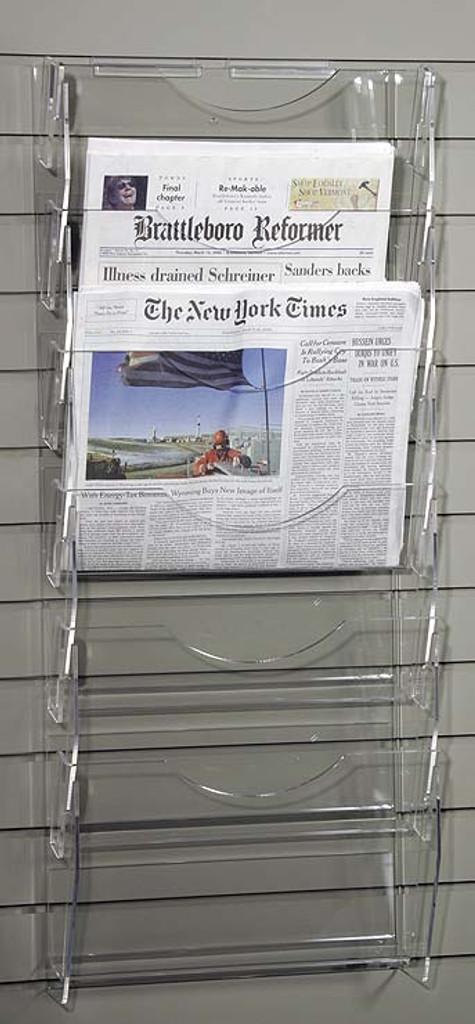 Clear acrylic slatwall mounted newspaper rack with six pockets.