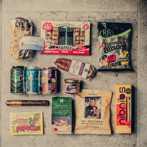 Our take on a manly modern tuck box. Some great examples of craft beers from Brooklyn, Beavertown and Brewdog. Some meaty and spicy nibbles with an over emphasis on pork and a sweet course of licorice, toffee and cookies. Oh, and a chocolate cigar to finish.