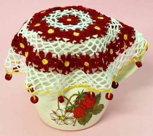 Crocheted jug cover featuring rings of daisy flowers, shown on jug.