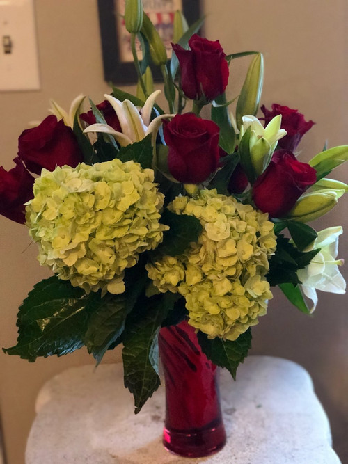 If she knows her flowers, she will love this arrangement:  hydrangeas, roses, lilies and stargazers all placed together in a shiny red metallic vase.