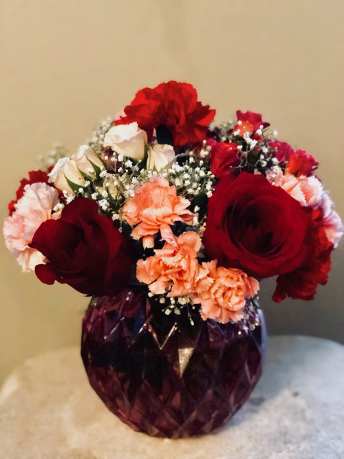 A collection of roses, carnations and babies breath all clustered together in a pink glass bubble bow.