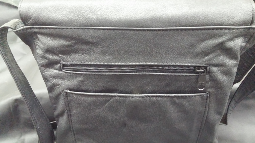 On the back we placed a zipper and below a roomy padded pocket large enough for most all large phones. It is secured with a magnetic closure.