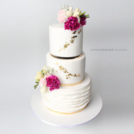 white and gold wedding cake with fresh flowers