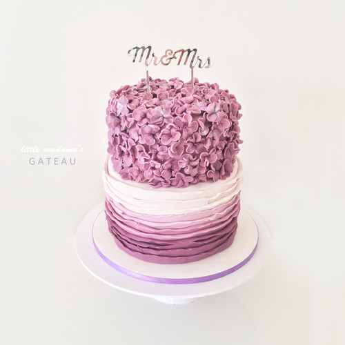 Purple sugar blossom with ombre ruffles wedding cake