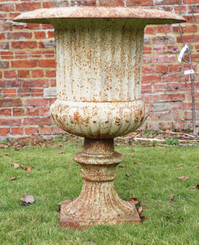 Large classical cast iron planter urn on plinth
