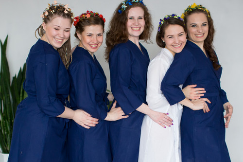 Bridesmaids in solid dark blue and bride in solid white getting ready robes