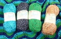 A selection of shades of Sirdar Amalfi dk yarn sitting on a top knitted from pattern 7775