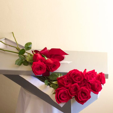 one dozen long stemmed red roses presented in a gift box