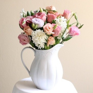 bunch of flowers arranged in a ceramic jug