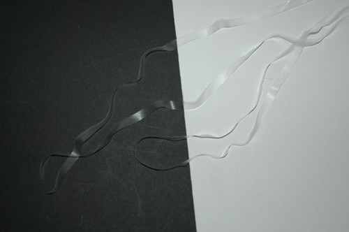 "1/4"" Clear Elastic - Festoon Elastic, 100% Polyurethane Elastic Laid Flat on Black and White to Show"