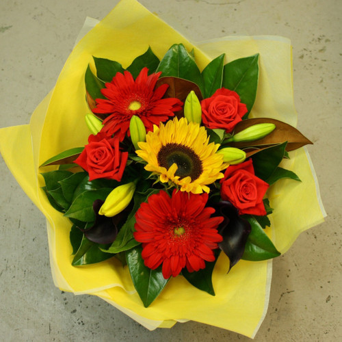 Vibrant bouquet of callas, gerberas, lilies, roses and sunflowers with seasonal foliage.