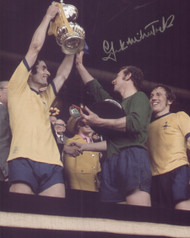 "Frank McLintock proudly lifts the FA Cup. Arsenal overcame Liverpool in the Final on their way to achieving a league and cup double in the 1970-71 season. The photograph is 12"" x 8"" (305mm x 205mm) and has been signed in silver sharpie marker by Frank McLintock."