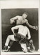 """On offer is an original radio/wire photograph showing World Heavyweight Champion Floyd Patterson in action as Tom McNeeley drops to one knee in the first round of their title fight held on December 4, 1961 at Maple Leaf Gardens in Toronto. Patterson retained his title after finally knocking McNeeley out in the fourth round.  Superb 8"""" x 6"""" (205mm x 150mm approx) picture and great addition to any boxing collection."""