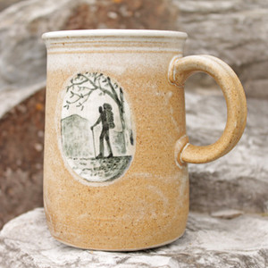 The mug features a hiker, or several, in an oval trail scene and is   signed by the potter on the bottom.