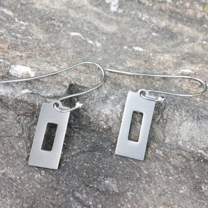 A pair of trail-marking blaze shape cut into rectangle earrings of recycled stainless steel.