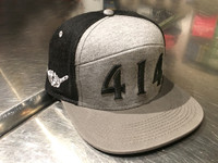 Walk down the high street with this 414 fashion hat. 96% breathable cotton denim high crown hat. Structured square visor in black. Heather heritage flannel front panel 4% acrylic. Milwaukee skyline print under visor. Adjustable snapback hat.