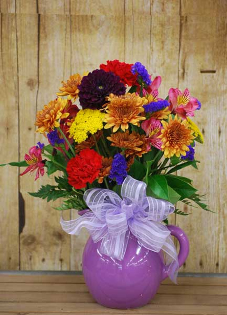 Fresh Arrangement of flowers that are Bright and Colorful in a Pitcher
