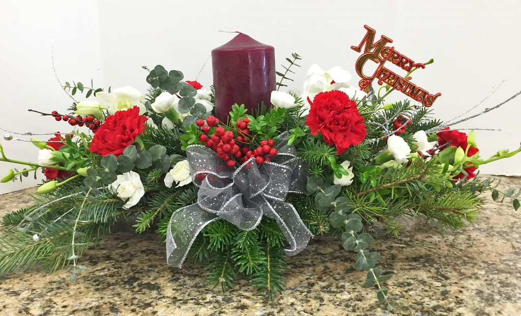 holiday centerpiece with pillar candle and fresh flowers