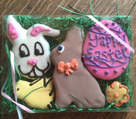 Clear holiday gift box featuring 5 treats.  One bunny face with pink ears, on small yellow chick outlined in carob, one large Easter bunny treat with a colored bow around it's neck, one Easter egg that says Yappy Easter in color coordinated writing and one miniature daisy shaped cookie fully covered and outlined in a coordinating color.