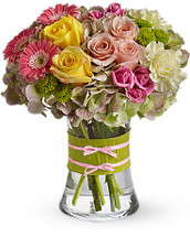 Flowers are always in fashion! Especially this chic mix of pinks, greens and yellows, arranged in a style evoking the English hand-tied bouquet. It's a stylish surprise for any lucky lady. Mini pink gerberas, lush green hydrangea, yellow and pink roses, yellow carnations and green button mums are arranged in a clear concave vase that's trimmed with a chartreuse taffeta ribbon and pink raffia.
