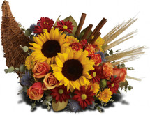 Dazzling sunflowers, light orange roses and spray roses, red daisy spray chrysanthemums, yellow cushion spray chrysanthemums, eucalyptus, magnolia leaves, cinnamon sticks and wheat are perfectly arranged in a wicker cornucopia. Now you know why cornucopia translates to the horn of plenty.