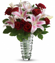 "The lush Valentine's Day bouquet includes red roses and pink oriental lilies accented with assorted greenery. Delivered in a contemporary glass vase with a sculpted ring design and featuring a weighted base. Approximately 17"" W x 20"" H"