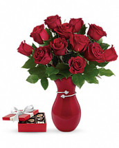 This sweet gift set includes a delicious box of chocolates paired with a stunning bouquet. Make her heart beat a little faster with this showstopping testament to true love! Gorgeous red roses, hand-delivered in a beautiful red vase with a box of chocolates, will make this Valentine's Day one to remember. This gorgeous arrangement features classic red roses and fresh lemon leaf. Delivered in a Pair of Hearts vase with a box of chocolates. Orientation: All-Around